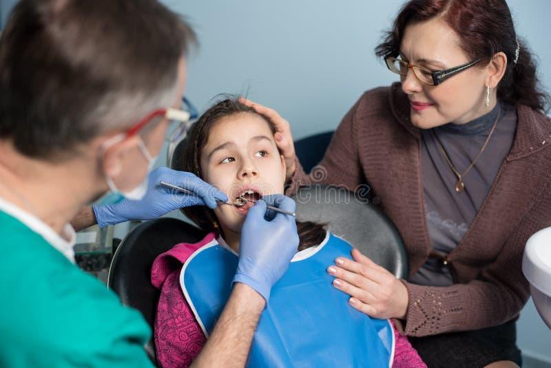 有母亲的女孩第一次牙齿参观的 做患者的资深小儿科牙医第一核对 库存图片