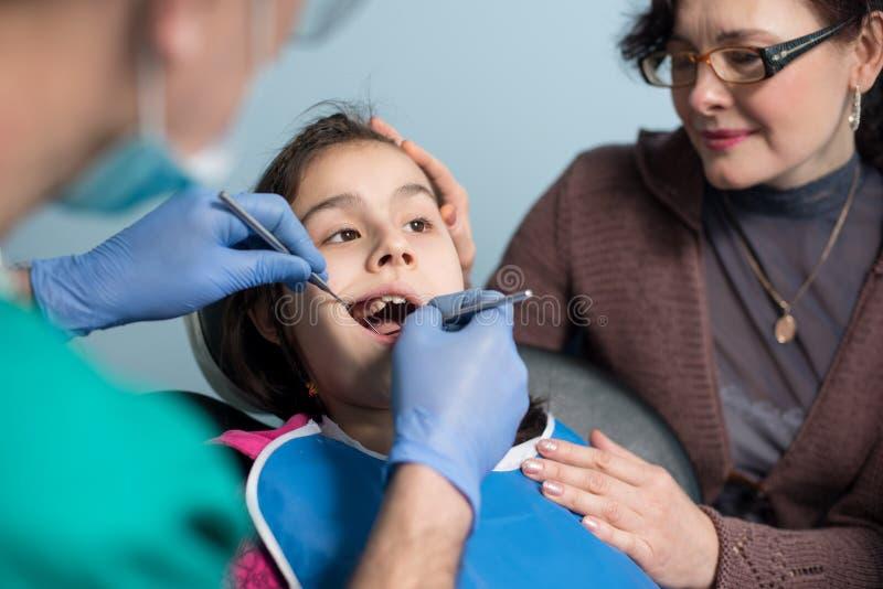 有母亲的女孩第一次牙齿参观的 做患者的资深男性牙医第一核对在牙齿办公室 免版税库存图片