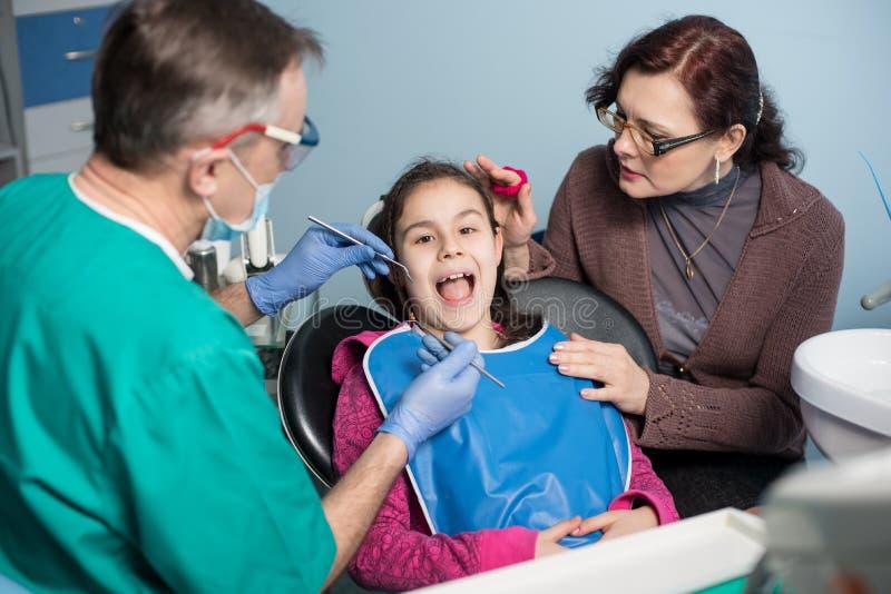 有母亲的女孩第一次牙齿参观的 做患者的资深男性牙医第一核对在牙齿办公室 免版税图库摄影
