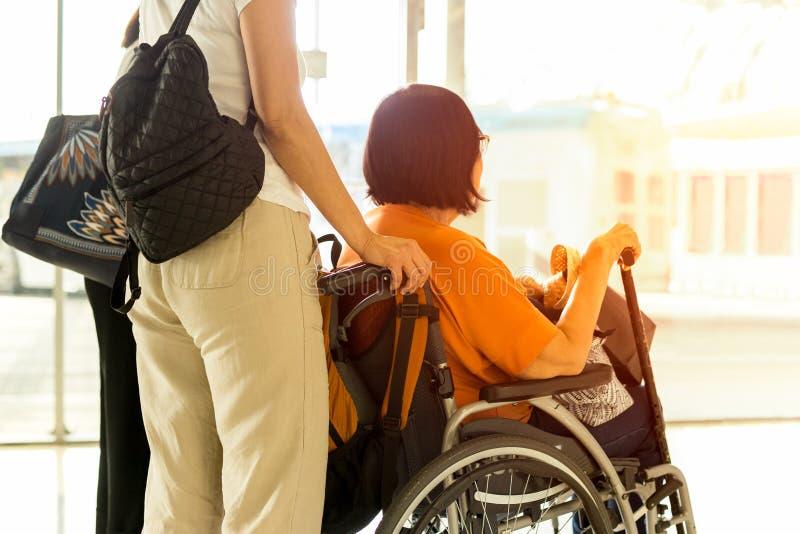 有母亲的妇女轮椅等待的搭乘的在国际机场 免版税库存图片