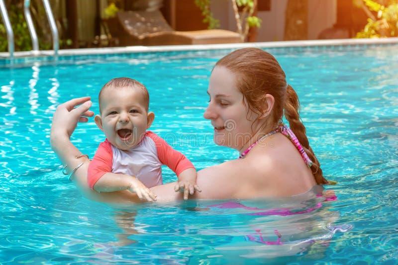 有母亲的愉快的小孩,被铭记婴孩的第一次在一个大水池和非常 婴儿非常愉快和欢乐 免版税库存图片