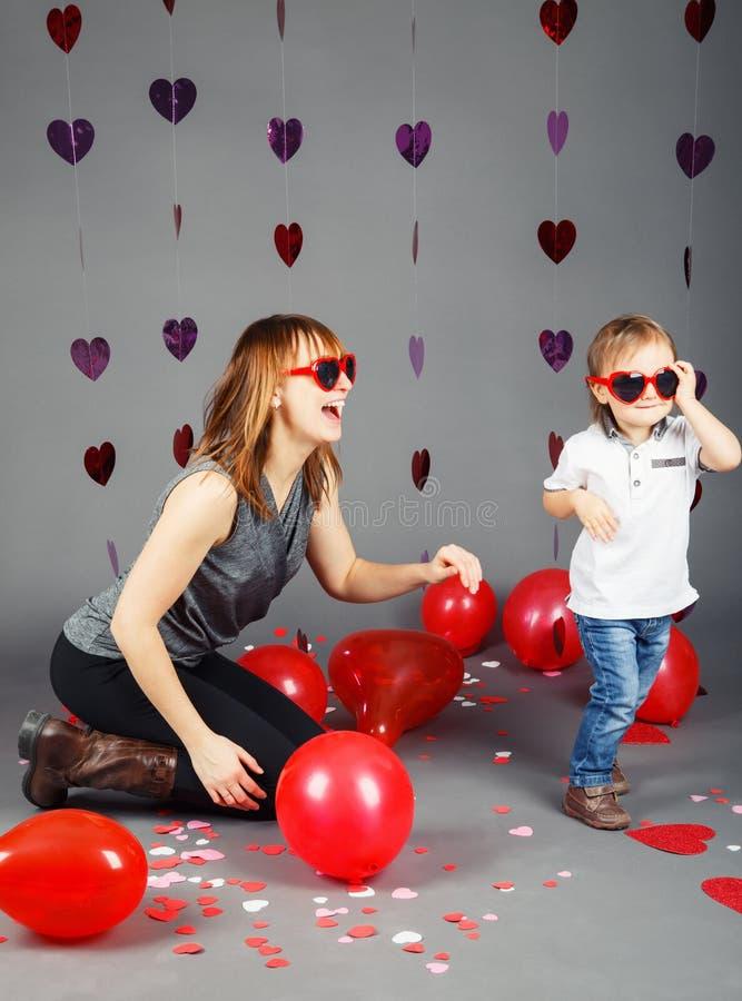 有母亲的男婴小孩在佩带滑稽的玻璃微笑的笑的演播室获得乐趣 免版税图库摄影