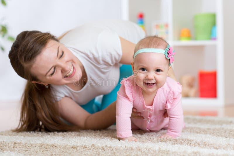有母亲的滑稽的爬行的女婴 免版税库存照片