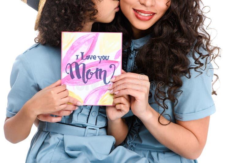有母亲节贺卡的亲吻她的母亲的女儿播种的射击隔绝在白色 免版税图库摄影