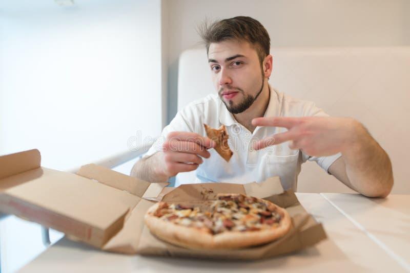 有比萨饼的一个英俊的人在他的手上在照相机摆在 供以人员坐在桌上靠近薄饼箱子 图库摄影