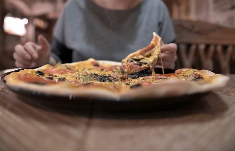 有比萨饼的女性手,以咖啡馆为背景 免版税库存图片