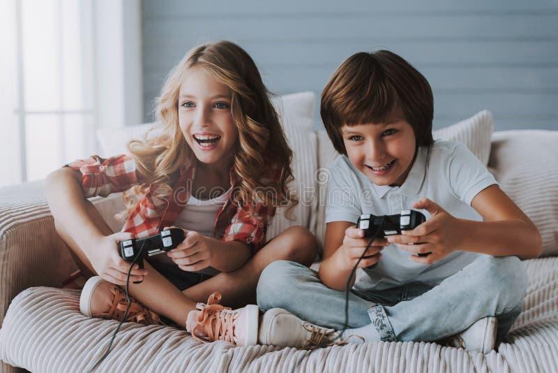 有比赛控制器的快乐的孩子在家打电子游戏 库存照片