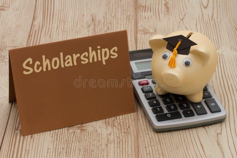 有毕业盖帽、卡片和计算器的金黄存钱罐在木头b 免版税库存照片