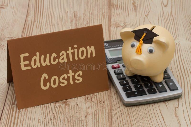 有毕业盖帽、卡片和计算器的金黄存钱罐在木头b 免版税库存图片