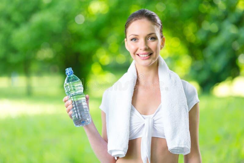 有毛巾和瓶的女运动员水 免版税库存照片