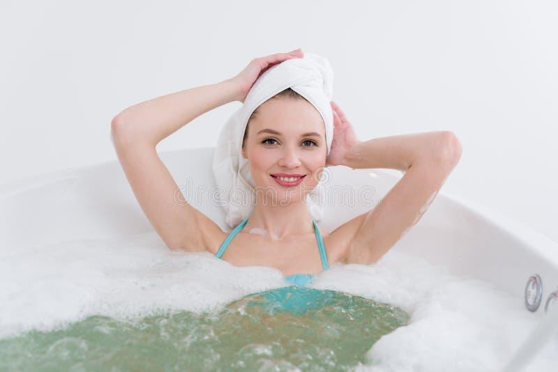 有毛巾的可爱的妇女在顶头放松在浴 免版税库存照片