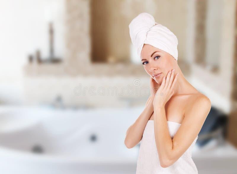 有毛巾的妇女在有极可意浴缸的卫生间里 免版税库存照片