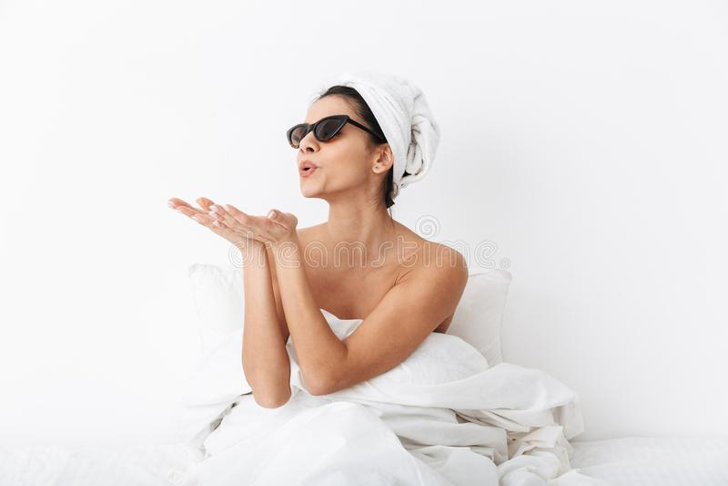 有毛巾的妇女在顶头谎言在床上在毯子下被隔绝在白色送飞吻的墙壁背景佩带的太阳镜 库存图片