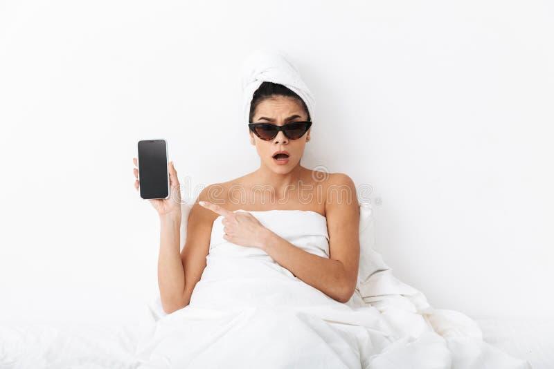有毛巾的惊奇的情感妇女在顶头谎言在床上在毯子下被隔绝在白色墙壁背景佩带的太阳镜 图库摄影