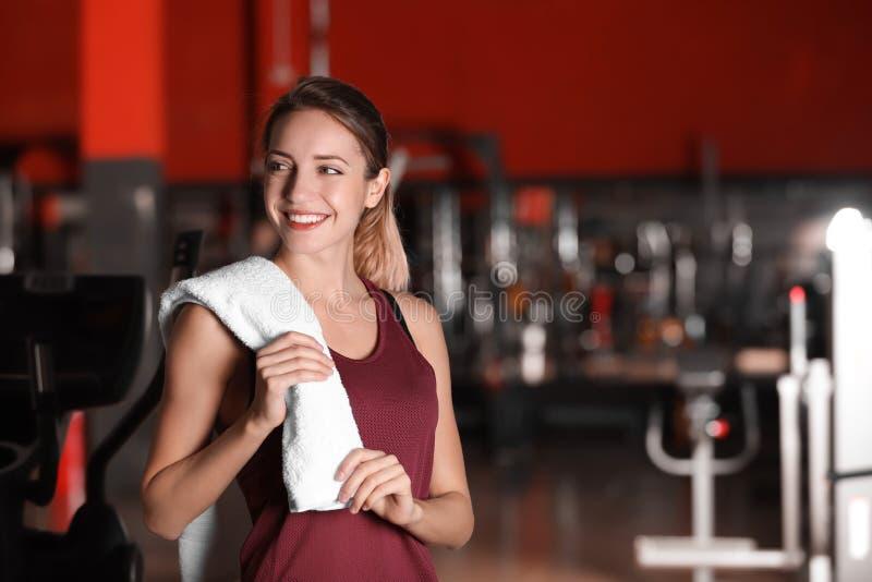 有毛巾的美丽的年轻女人在健身房 库存照片