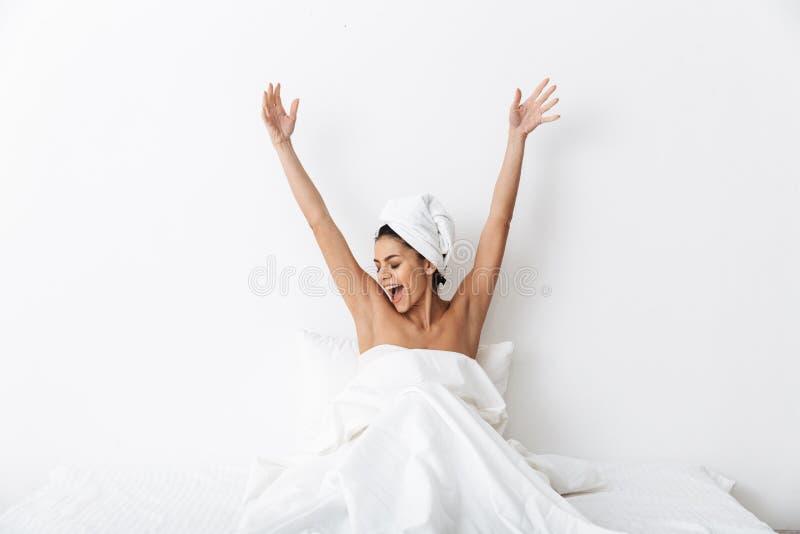 有毛巾的美丽的惊人的妇女在顶头谎言在床上在毯子下被隔绝在白色墙壁背景 图库摄影
