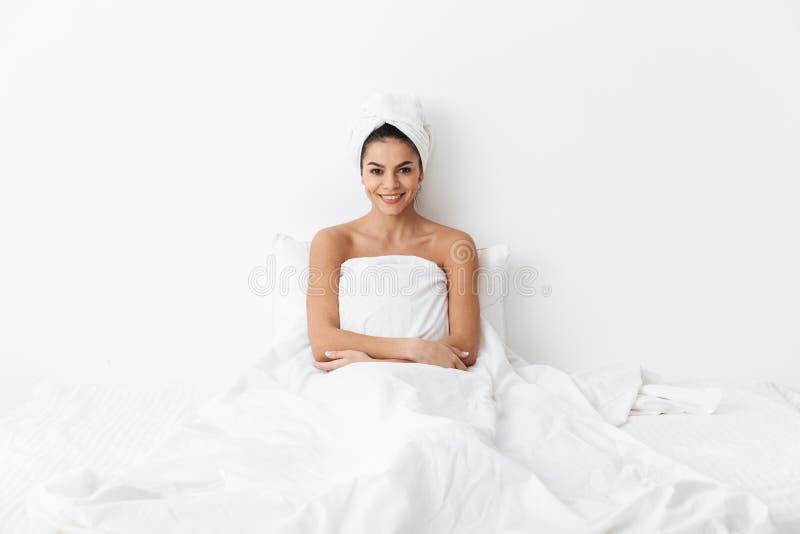 有毛巾的美丽的惊人的妇女在顶头谎言在床上在毯子下被隔绝在白色墙壁背景 库存图片
