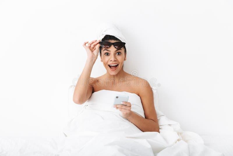 有毛巾的美丽的惊奇的情感妇女在顶头谎言在床上在毯子下被隔绝在白色墙壁背景佩带 免版税库存图片