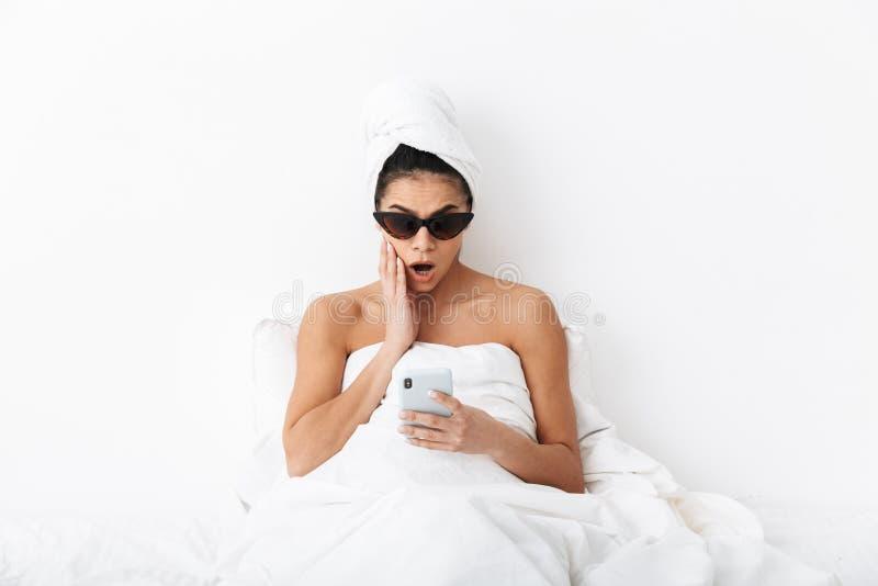 有毛巾的美丽的惊奇的情感妇女在顶头谎言在床上在毯子下被隔绝在白色墙壁背景佩带 免版税图库摄影