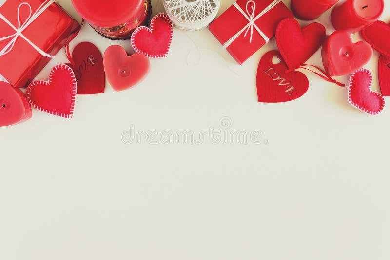 有毛毡爱心脏和蜡烛的当前箱子在白色木背景 华伦泰` s天庆祝概念 顶视图 平的位置 免版税库存照片