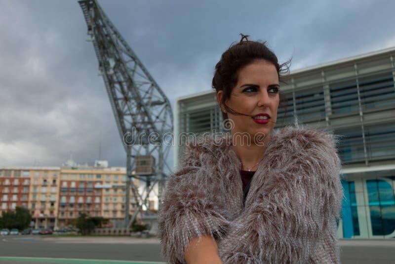 有毛皮大衣画象身分外部的深色的妇女,与一台港起重机在背景中 库存照片