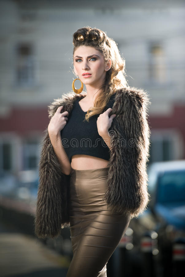 有毛皮海角的可爱的少妇在都市时尚射击。有紧身衣裳的美丽的时兴的女孩 免版税库存图片