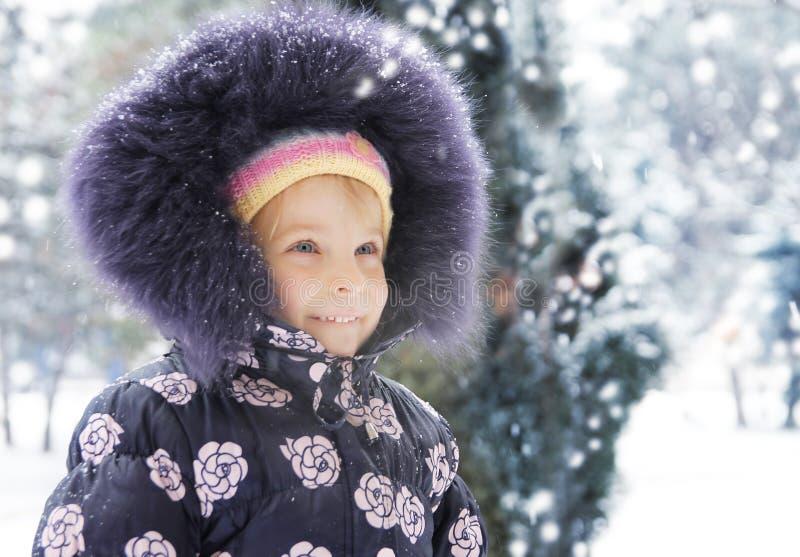 有毛皮的女孩享用雪的 免版税库存图片