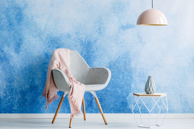 有毯子、现代咖啡桌、花瓶和灯的灰色扶手椅子 免版税库存图片