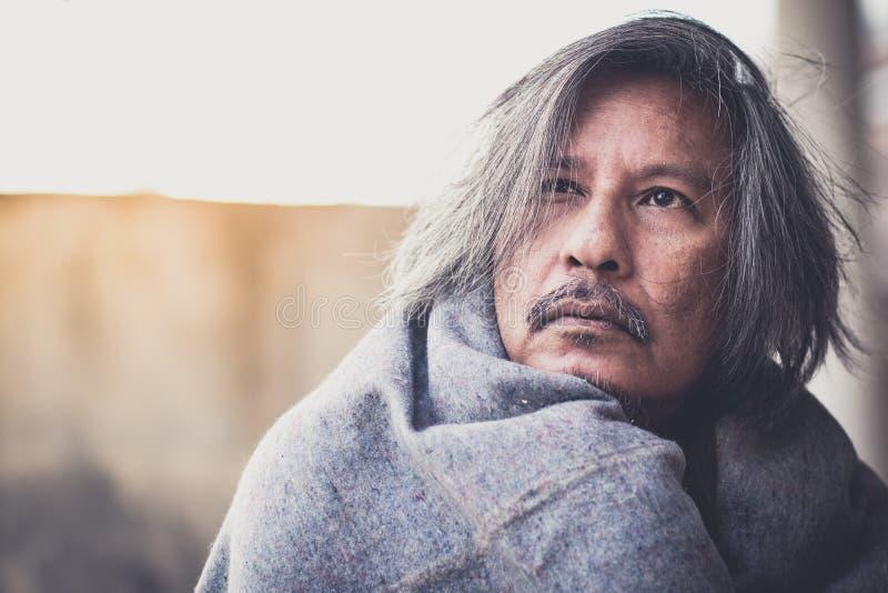 有毯子的无家可归的人在城市等待的仁慈人民的走道街道上给金钱或食物 他冷 免版税库存照片