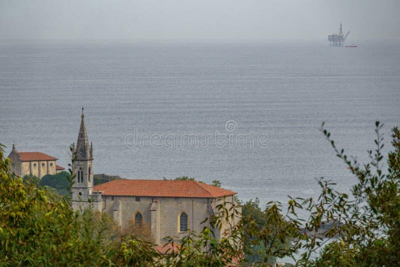 有气体海洋平台的Mundaka教会在天际 图库摄影