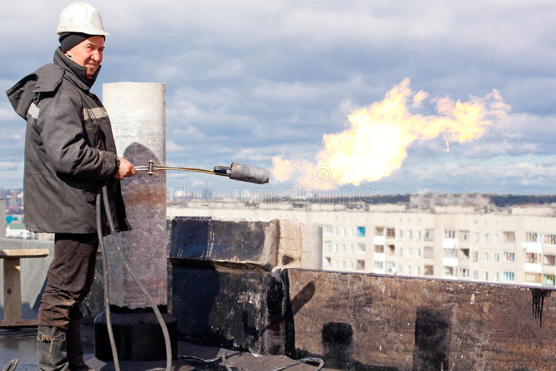 有气体火炬的正屋面防水工工作员 免版税库存图片