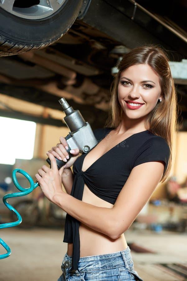有气动力学的钥匙的画象妇女在液压悬挂的汽车下 免版税库存图片