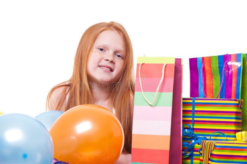 有气球和礼物盒的红头发人女孩 免版税库存照片
