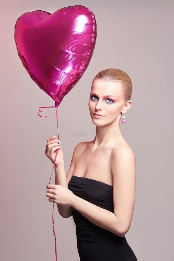 有气球心脏的美丽的妇女 免版税库存照片