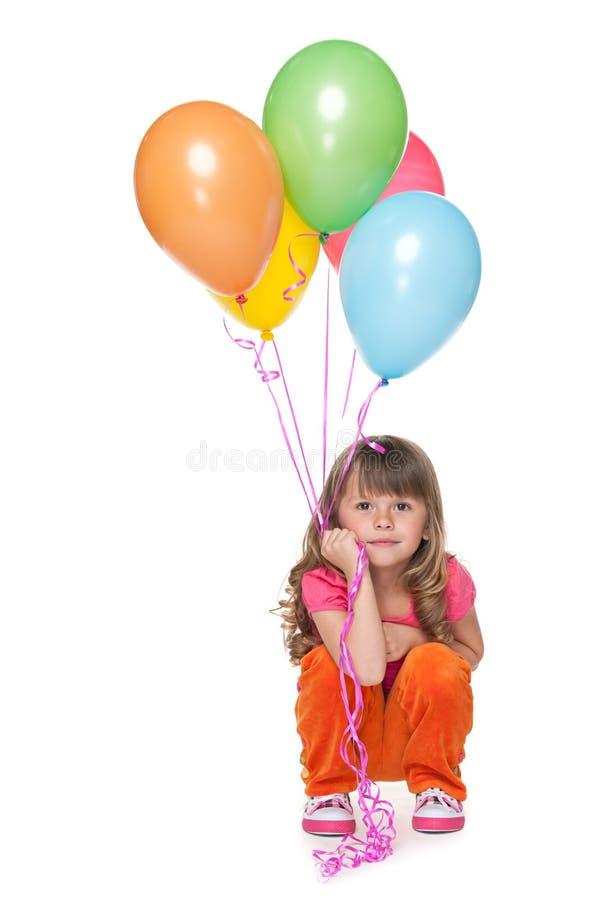 有气球的体贴的小女孩 免版税库存图片