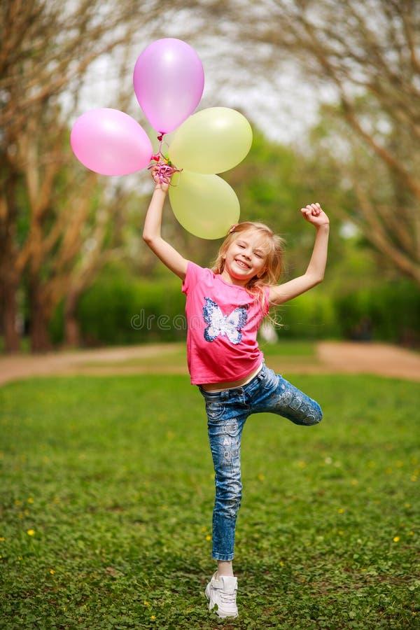 有气球的愉快的女孩跳跃在城市公园庆祝夏天自然的生活方式生气勃勃的 免版税库存照片