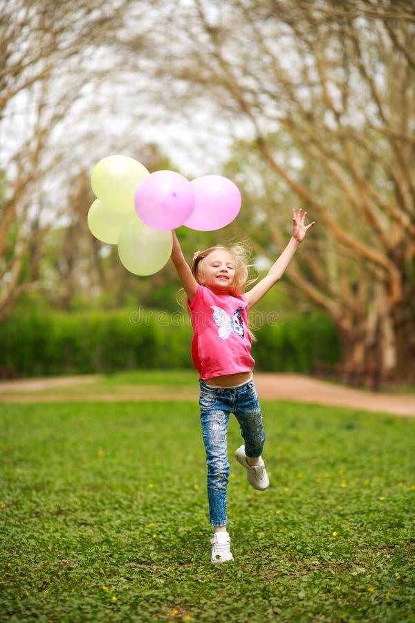 有气球的愉快的女孩跳跃在城市公园庆祝夏天自然的生活方式生气勃勃的 库存照片