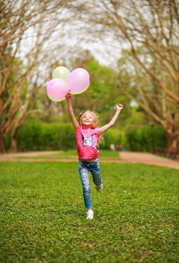 有气球的愉快的女孩跳跃在城市公园庆祝夏天自然的生活方式生气勃勃的 库存图片