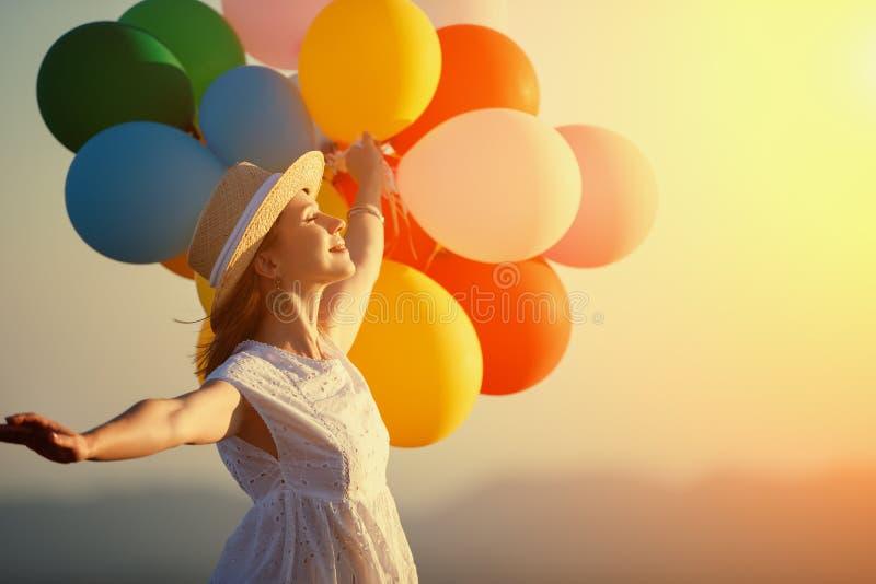 有气球的愉快的妇女在日落在夏天 免版税库存照片