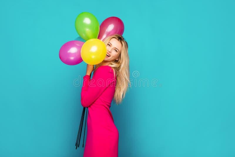 有气球的白肤金发的妇女在蓝色 库存图片