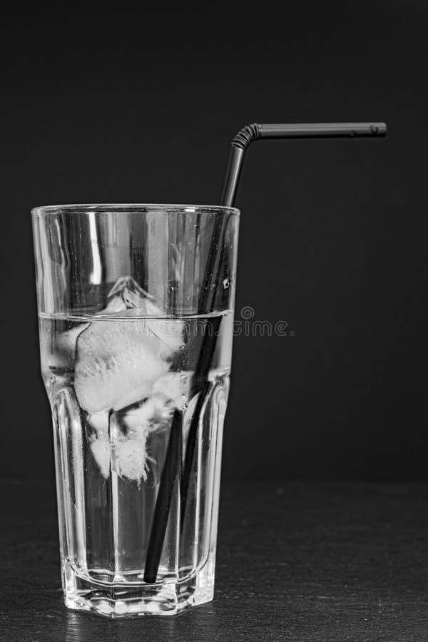 有水、冰块和黑秸杆的玻璃杯子在黑背景 库存照片