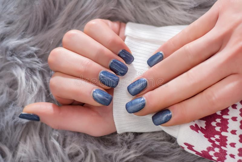 有水军蓝色指甲油颜色的女孩手在冬天毛线衣 免版税库存图片