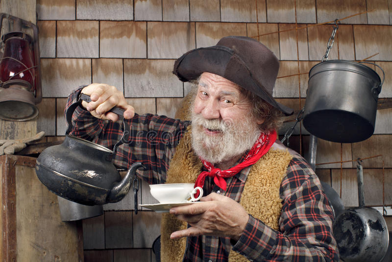 有水壶和瓷茶杯的快乐的老牛仔 免版税库存图片