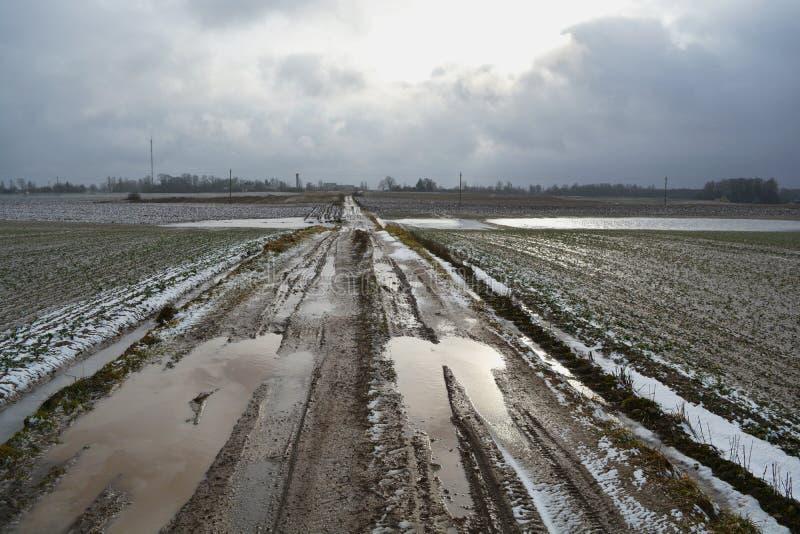 有水水坑和冰的坏春天农田路 免版税库存照片