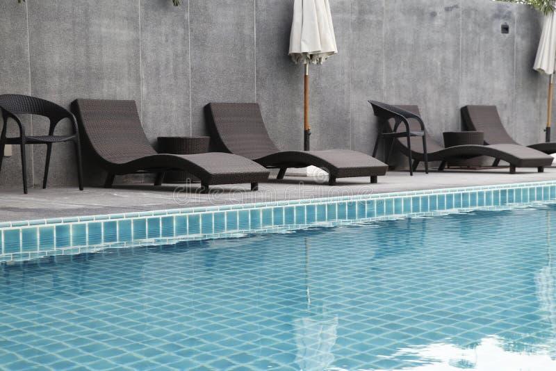 有水池椅子集合和伞的游泳场 免版税库存图片