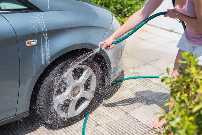 有水管的少妇洗涤的汽车 汽车详述 免版税库存照片