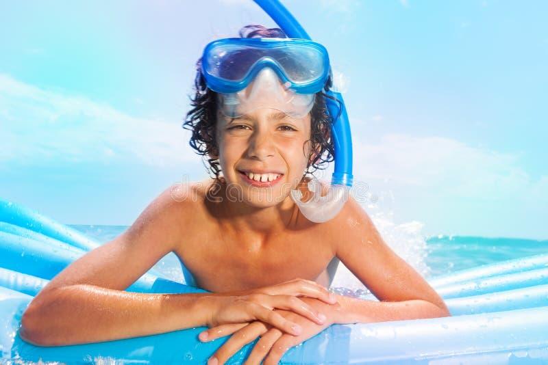 有水肺面具游泳的男孩在matrass在海 免版税库存照片