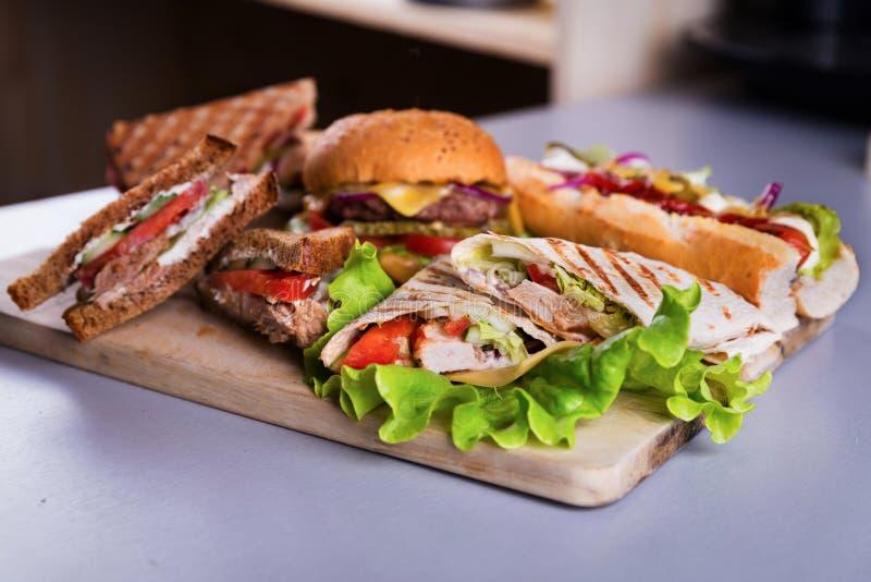 有汉堡热狗的快餐板材将鸡套夹在中间 免版税库存照片