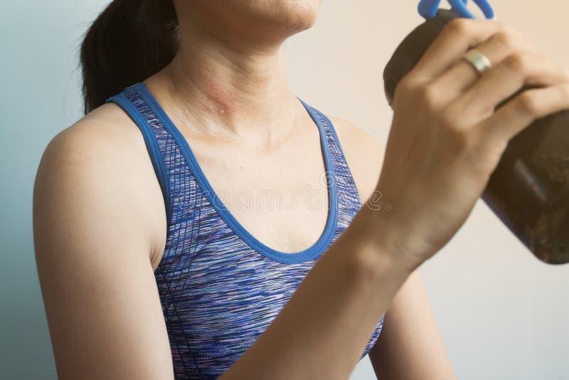 有汗水的妇女身体,饮用的蛋白质震动 库存图片