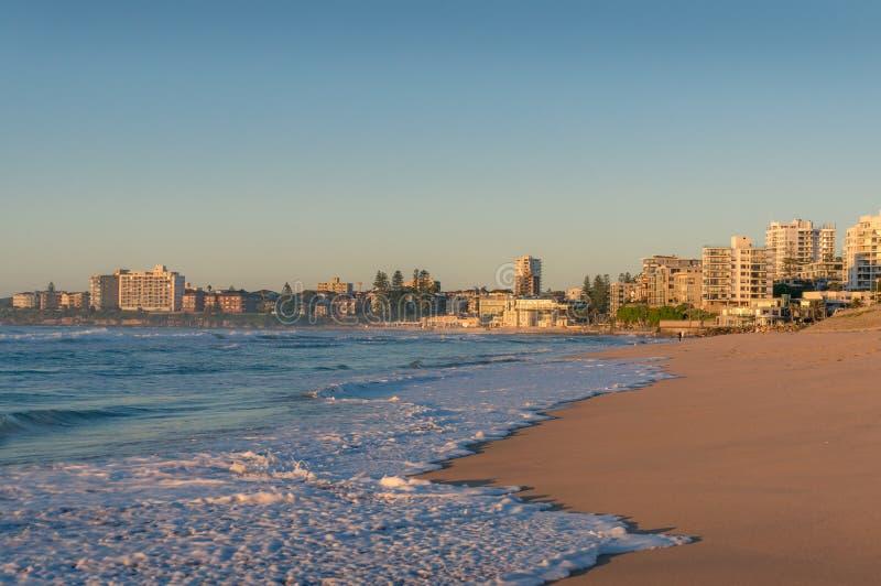 有江边物产的克罗纳拉海滩住宅区在日出 免版税库存图片